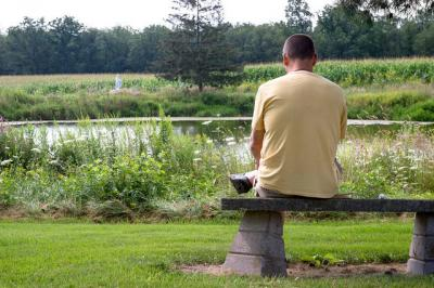 Doug Engelhart of Hiram, Ohio, reads next to the pond near Bethlehem Retreat House at the Abbey of the Genesee in Piffard Aug. 4.