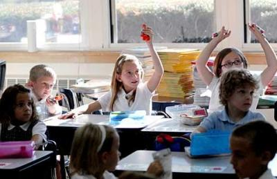 Students raise their hands on the first day of classes at St. Joseph School in Penfield in this Sept. 2008 file photo.