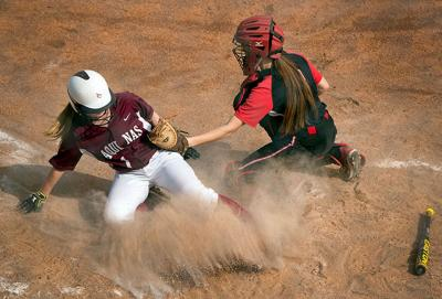 Megan Hildebrand slides safely into home plate to score in the fifth inning of Aquinas Institute's 5-3 loss to Geneva in the Section Five Class A2 championship game May 29 at the State University of New York at Brockport.