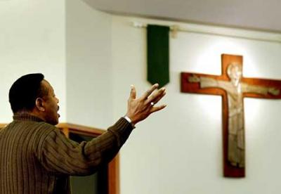 A parishioner raises his hands while worshiping at Rochester's St. Bridget's Church in this Jan. 2006 file photo.