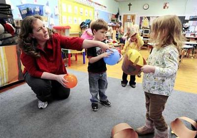 Diane Walsh, who currently has four children attending  St. Ann School in Hornell, volunteers at the school whenever she can. Above, she lends a hand Jan. 22 in the preschool class of her 3-year-old son Kodiak (center).