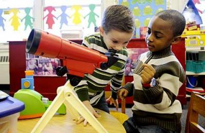 Kindergartners Sean Riley (right) and Ben Sargent look through a toy telescope during instructional-focused play time Jan. 19 at Christ the King School in Irondequoit. Teacher Helene Coon says playing together helps her students learn important social skills.