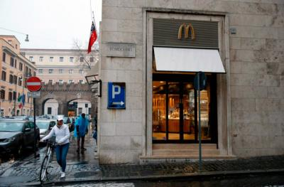 """A worker crosses the street with her bike outside the newly opened McDonald's near the Vatican Jan. 12. The McDonald's will collaborate with Italian aid organization, """"Medicinia Solidale,"""" and the papal almoner's office to help feed the poor and homeless around the Vatican."""