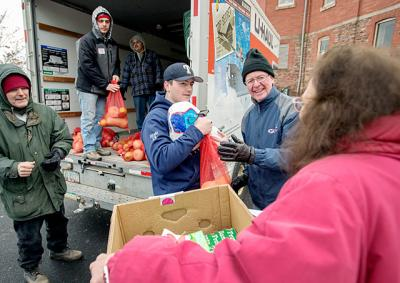 Dan Cass (right) and 16-year-old Brandon Zicari (center) were among many volunteers who gave food to needy community members during HOPE Ministry's annual Christmas distribution at Webster's Holy Trinity Church Dec. 20.