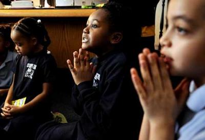 Second-graders Tia Rolle (from left), Brianna Jones and Isaiah Pacheco pray before having a snack during a reading activity Feb. 4 at Rochester's Cathedral School at Holy Rosary.