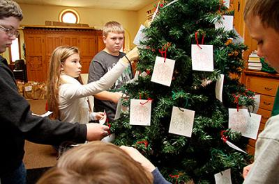 Faith-formation students Dylan Wilder (from left), Celia Mattie, Aiden Tardif and Ryan Gilbert decorate a giving tree at Auburn's Holy Family Church Nov. 24.