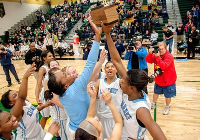 Members of Bishop Kearney's girls' basketball team players hoist the Section Five Class B2 championship trophy after beating Batavia Notre Dame 55-31 March 1 at Rush-Henrietta Senior High School.