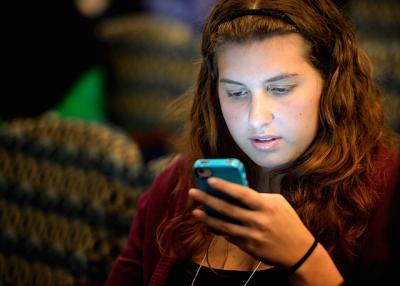 A young woman tweets during a 2012 conference in Washington. Area Catholic schools are using such social media outlets as marketing tools.