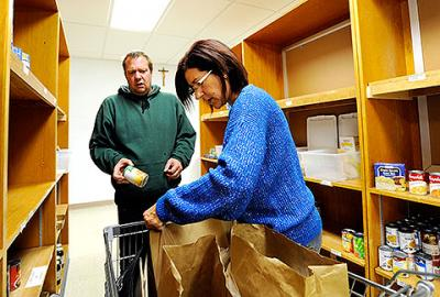 Volunteer Lisa Wilson helps Ronald Thorpe pick out food from the shelves of St. Theodore's Food Cupboard Oct. 29.