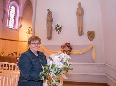 Karen Mulry holds a purple orchid corsage, similar to one placed on the statue of Mary, seen in the background May 4, at St. John Nepomucene Church in Little Chute, Wis. An anonymous request to place flowers on the statue for Mother's Day has been sent to Reynebeau Floral in Little Chute for 70 years.