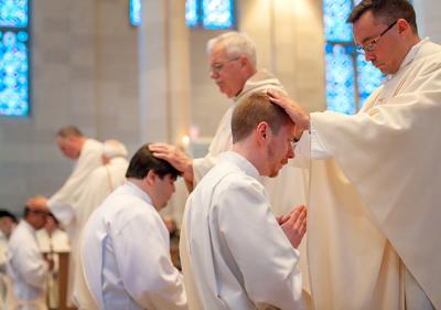 Diocesan priests, including Father Peter Clifford (center) and Father Matthew Jones (right), lay their hands on the heads of newly ordained priests Fathers Jainer Erick Viloria (from left), Jorge Ivan Ramirez and Justin Miller during the June 4 ordination Mass at Rochester's Sacred Heart Cathedral.