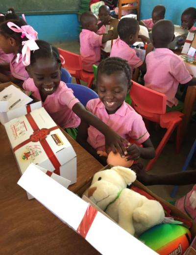 Children in Les Cayes, Haiti, open presents March 22 that they received through the Box of Joy program of Cross Catholic Outreach, a Florida based relief and development agency.