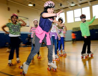 Fourth-grader Alivia Gorre (front) races around the gymnasium Jan. 28 during roller-skating day at St. Lawrence School in Greece.