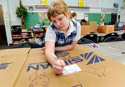 Third-grader Stephanie Gilbert decorates boxes to be used for pet donations during a Jan. 25 meeting of the Hands in Paws Club at Seton Catholic School in Brighton.
