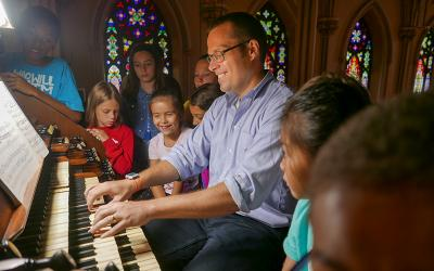 """<p>Jared Lamenzo, organist at the Basilica of St. Patrick's Old Cathedral in the Manhattan borough of New York, plays the parish's 1868 Henry Erben Pipe Organ for an audience of appreciative youngsters July 26 during the parish's five-day music camp, aptly titled """"Pipes, Pedals & Peals."""" Organizers hope to make the music camp an annual summer program.  </p>"""