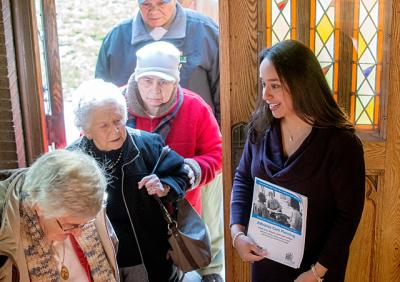 URMC resident Dr. Marielena Velez de Brown greets parishioners of Rochester's Our Lady of the Americas church before a Feb. 7 Mass. Dr. Velez conducted survey's following the Mass as part of her master's thesis on advanced-care directives.