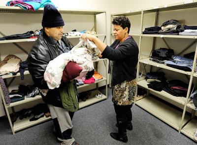 Monica Post helps a client pick out clothing and linens in 2012 at Catholic Family Center Community Resource Services in Rochester.