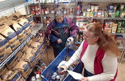Clients select grocery items at the Catholic Charities of Steuben County food pantry in Bath in 2004. Officials say more working poor are utilizing the food pantries because of the recent recession.