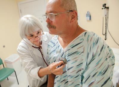 Ginger Krebbeks, a nurse practitioner, examines patient Miguel Berrios Aug. 26 at St. Joseph's Neighborhood Center in Rochester. The center is gearing up to help patients as provisions of the Affordable Care Act are implemented.