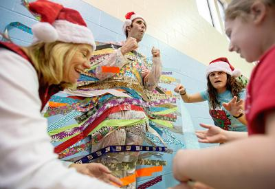 Principal Frank Arvizzigno entertains students at Greece's St. Lawrence School as librarian Jeannine Fraser (left) and physical education teacher Breanne Toscano direct the placement of colorful duct tape to hold him to the wall Dec. 17.
