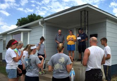 Volunteers with the Prayer and Action summer mission program of the Diocese of Salina, Kan., prays with Father Jarett Konrade and a homeowner in Stockton, Kan., June 4.