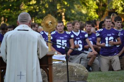 Players from Cincinnati Elder High School pray July 30 with Father Benedict O'Cinneslaigh of Mount St. Mary's Seminary of the West at the Athenaeum of Ohio. SportsLeader, a Louisville,Ky.-based coach training and formation company, has been organizing rosary rallies for high school football players across the nation.