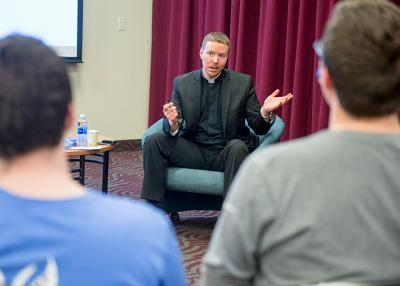 During an April 3 presentation at St. John Fisher College, Father Justin Miller talks with students about his journey from being a freshman at Fisher to becoming a diocesan priest.