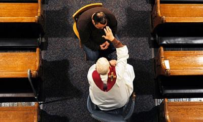 In this image from 2009, Father Laurence Tracy blesses a man after hearing his confession.