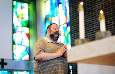 Joe Del Plato, who receives outpatient services at the Rochester Psychiatric Center, prays during a May 22 Mass at the center.