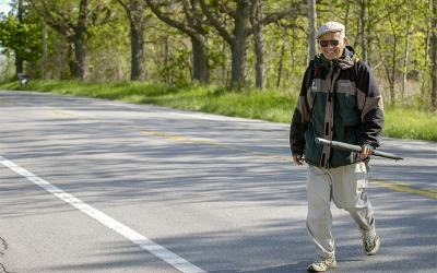 Father Bill Brown walks from Brockport to Bergen along Route 19 May 23, 2003 as part of his trek through New York to raise money for missions in Peru. (Courier file photo)