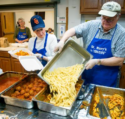 Bob Steigerwald pours pasta into a pan as Sandy Lent waits to fill a take-out order during a May 7 dinner at St. Mary Parish in Auburn. The parish has held monthly pasta dinners for the past 18 years.