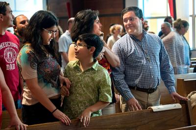 Victoria (from left) Antonio, Rita and José Rivera offer each other the sign of peace during a May 28 Mass at St. Leo Parish in Hilton. The Rivera family, which also includes son Carlos and daughter Ana, recently won the New York state Knights of Columbus Family of the Year award.