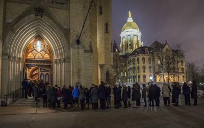 <p> Students wait in line outside the Basilica of the Sacred Heart on the campus of the University of Notre Dame in 2015. <p>