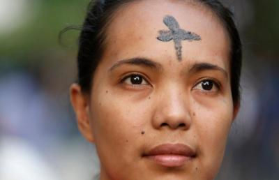 A woman with a cross marked on her forehead looks on during Ash Wednesday Mass in 2014 in Manila, Philippines. On Ash Wednesday, it's not hard to identify Catholics. The smudge of ashes in the shape of a cross on their foreheads is a solid giveaway. (CNS photo by Erik De Castro/Reuters)