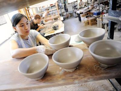 Potters at the Rochester Folk Art Guild in Middlesex, N.Y. throw bowls for a Catholic Charities of the Finger Lakes Empty Bowls event in this 2010 photo.