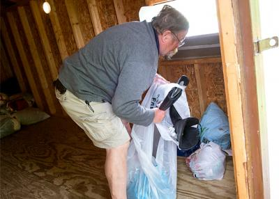 Wally Lannon moves donated items inside a St. Pauly Textile drop-off shed at St. Dominic Church in Shortsville May 26. Lannon checks the shed each day to keep it organized and make it easier for the weekly pick-up of items.